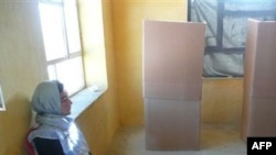 Một nhân viên phòng phiếu ngồi canh giữ 1 thùng phiếu ở Bamyan, Afghanistan, 18/9/2010