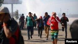Мігранти прикривають свої обличчя, втікаючи від сльозогінного газу, застосованого прикордонним патрулем США біля огорожі між Мексикою та Сполученими Штатами в Тіхуані, Мексика, 25 листопада 2018 року.