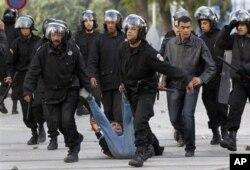 Un manifestant interpelé par la police anti-émeute, vendredi, à Tunis