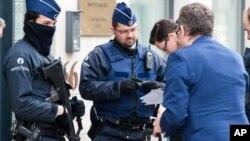 Polisi memeriksa identitas orang-orang yang akan memasuki gedung pemerintah di Brussels, Belgia (16/1). (AP/Geert Vanden Wijngaert)