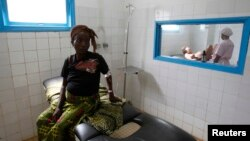FILE - A pregnant woman waits while another goes into labor at a general hospital.
