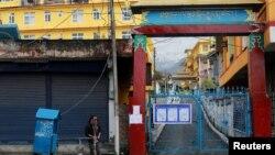 Seorang pria mengisi embernya dengan air di luar Biara Tantrik Gyuto yang ditutup selama sebulan di tengah ketakutan merebaknya virus corona di Dharamsala, India, 12 Maret 2020.