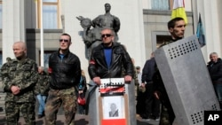 Para anggota kelompok sayap kanan ultra nasionalis Right Sector, berdiri di depan gedung parlemen di Kiev, Ukraina, 28 Maret 2014 (Foto: dok/ AP Photo/Sergei Chuzavkov).