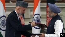 Afghanistan's President Hamid Karzai and India's Prime Minister Mamohan Singh exchange documents after signing a joint statement at Hyderabad House in New Delhi, October 4, 2011.