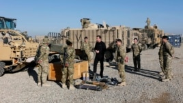 Britain's Prime Minister David Cameron chats with soldiers in front of Mastiff armored vehicles at Camp Bastion, outside Lashkar Gah, in Helmand Province, Afghanistan, Dec. 20, 2012.