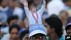 A supporter sports a cut-out of Sri Lankan President Mahinda Rajapaksa on his head, during Rajapaksa's final public rally for the presidential elections in Kesbewa, about 20 kilometers (12 miles) southeast of Colombo, Sri Lanka, Monday, Jan. 5, 2015.