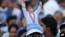 Topi berbentuk Presiden Sri Lanka Mahinda Rajapaksa yang dipakai seorang pendukungnya dalam kampanye pilpres di Kesbewa, sekitar 20 kilometer dari Kolombo, Sri Lanka (5/1). (AP/Sanka Gayashan)