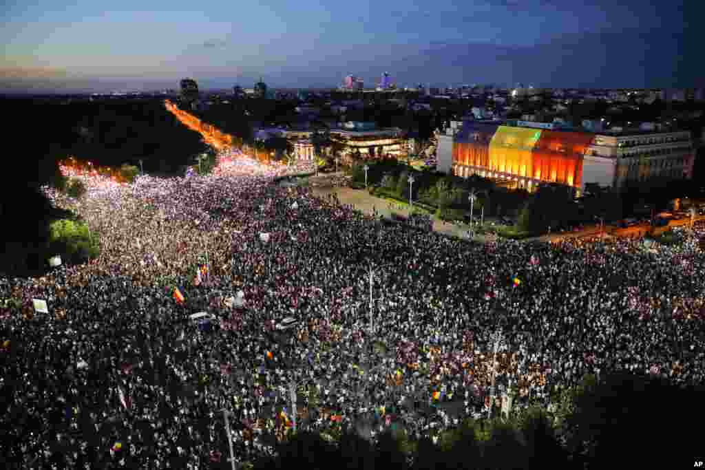 People shine the lights of their mobile phones during protests outside the government headquarters, seen at right, in Bucharest, Romania. Romanians who live abroad are staging an anti-government protest calling on the left-wing government to resign and an early election.