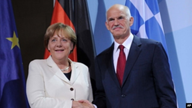 German Chancellor Angela Merkel and the Prime Minister of Greece, Georgios Papandreou shake hands prior to a dinner at the chancellery in Berlin, Germany, Sept. 27, 2011.