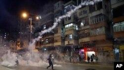 Para demonstran berlarian menghindari gas air mata yang ditembakkan oleh pasukan keamanan dari markas polisi Shum Shui Po, Hong Kong, Rabu malam (14/8).
