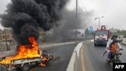 Một chiếc xe bị người biểu tình đốt cháy trên đường phố Karachi ở miền nam Pakistan