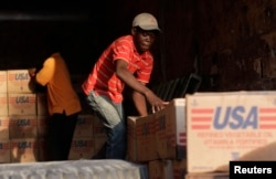 Americans donated more than $1.4 billion to nearby Haiti after a devastating earthquake in January 2010. Here, men stack supplies in Port-au-Prince on March 17, 2010.