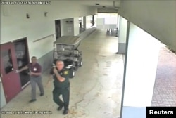 FILE - Then-Broward County Sheriff's Deputy Scot Peterson, who was assigned to Marjory Stoneman Douglas High School during the Feb. 14, 2018 shooting, is seen in this still image captured from the school surveillance video released by Broward County Sheriff's Office in Florida, March 15, 2018.