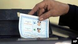 一名埃及选民在开罗的投票站投下了总统选举的选票。(2018年3月26日)
