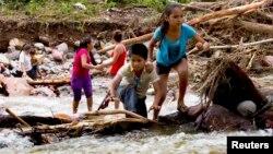 """Dos niños cruzan una quebrada en las montañas de Zihuatanejo, estado de Guerrero, luego del paso del huracán """"Manuel""""."""