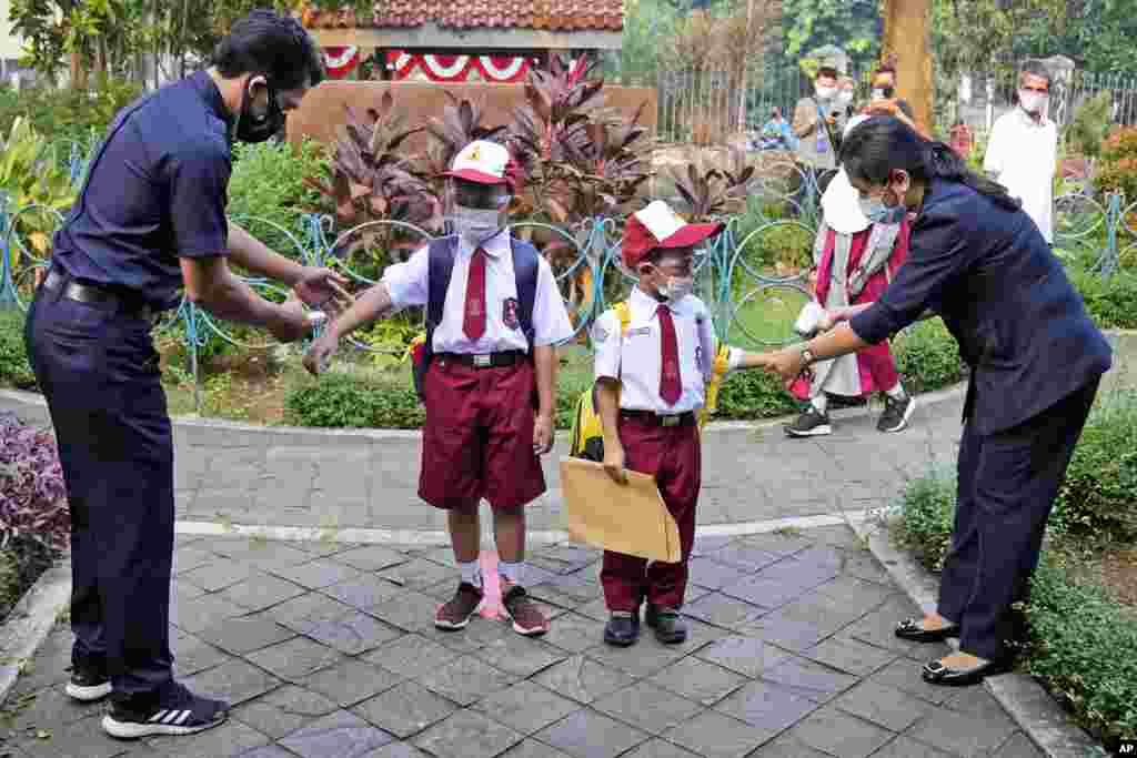Para guru memeriksa suhu tubuh siswa Sekolah Dasar pada hari pertama pembukaan kembali sekolah di Jakarta, Indonesia, Senin, 30 Agustus 2021. (Foto: AP / Dita Alangkara)
