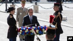 French President Francois Hollande, center, lays a wreath at the Tomb of the Unknown Soldier during commemorations at the Arc de Triomphe marking the 71st anniversary of the end of World War II, in Paris, May 8, 2016.