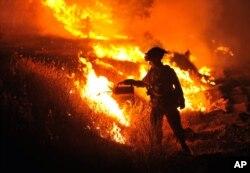 California firefighter Bo Santiago watches a backfire as the Rocky fire burns near Clearlake, California, Aug. 3, 2015.