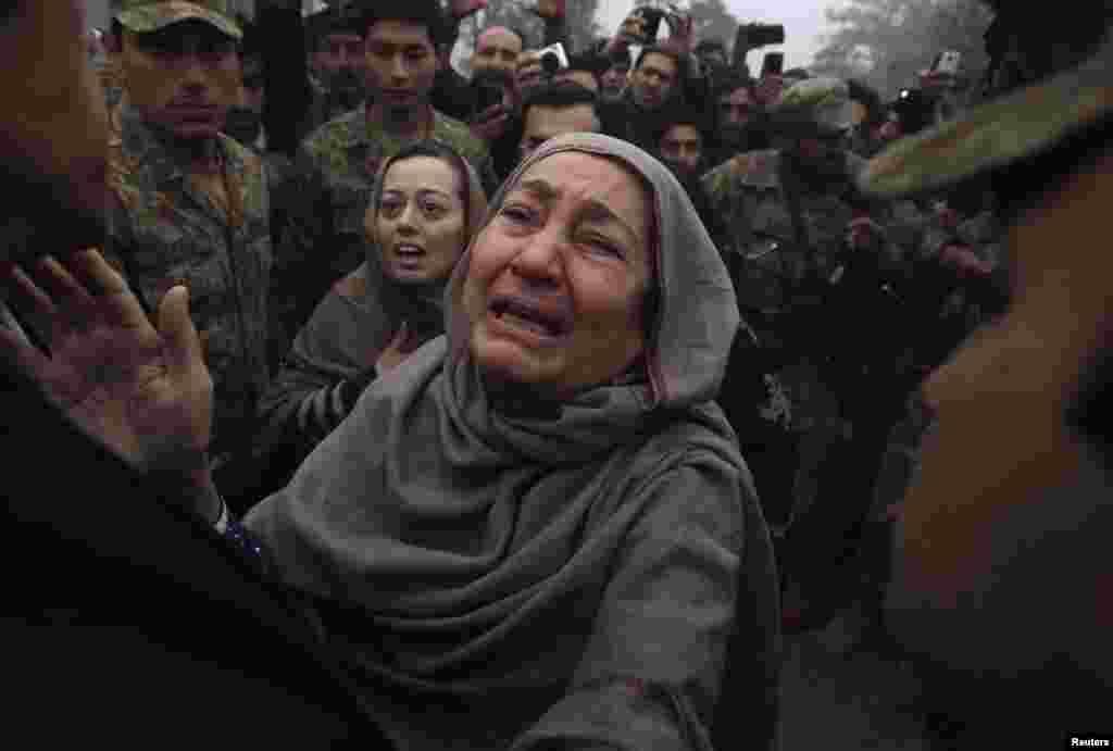 Bà (phải) và mẹ của Muhammad Ali Khan, một học sinh thiệt mạng trong vụ tấn công của những tay súng Taliban nhắm vào Trường Công lập Quân đội, biểu lộ sự đau buồn trong chuyến thăm của Imran Khan (trái), chủ tịch chính đảng Tehrik-e-Insaf của Pakistan, tại trường học ở Peshawar. Những tay súng Taliban xâm nhập vào trường và nổ súng vào ngày 16 tháng 12, 2014, giết chết 132 học sinh và chín nhân viên, các nhân chứng cho biết.