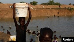 Seorang anak mengangkat ember yang berisi air di dekat kamp penampungan pengungsi PBB di Bentiu, Negara Bagian Unity, Sudan Selatan (17/6/2014).