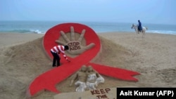 Seniman India, Sudersan Pattnaik, merapikan pahatan pasir pada malam peringatan Hari AIDS Sedunia di Pantai Laut Emas, di Puri, India, 29 November 2013. (Foto: AFP/Asit Kumar)