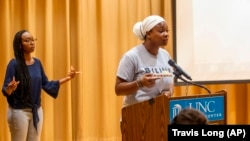"""De'Ivyion Drew, UNC-Chapel Hill student and community activist, right, speaks as Taliajah """"Teddy"""" Vann, president of the campus Black Student Movement, agrees with her message, during a press event held by the Black Student Movement, the Carolina Black Caucus and the Black Graduate and Professional Student Association on Wednesday, July 7, 2021, at UNC Chapel Hill's Sonja Haynes Center in Chapel Hill, N.C. (Travis Long/The News & Observer via AP)"""
