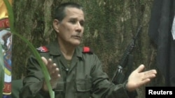 "FILE - National Liberation Army (ELN) commander Nicolas Rodriguez, known as ""Gabino,"" gestures as he speaks in response to questions from Reuters at a hidden jungle camp in this still image taken from an undated video released August 27, 2012."