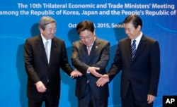 South Korea's Trade, Industry and Energy Minister Yoon Sang-jick, center, tries to hold hands to pose for the media with Japan's Economy, Trade and Industry Minister Motoo Hayashi, left, and China International Trade Representative Zhong Shan.