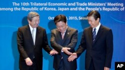 South Korea's Trade, Industry and Energy Minister Yoon Sang-jick, center, tries to hold hands to pose for the media with Japan's Economy, Trade and Industry Minister Motoo Hayashi, left, and China International Trade Representative Zhong Shan before the 1