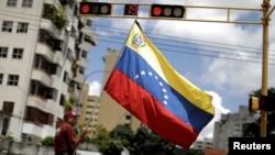 抗議者在參加一場抗議馬杜羅政府的罷工後站在首都卡拉卡斯的街頭高舉一面委內瑞拉的旗幟 (2017年7月29日)