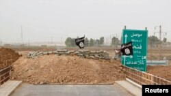 Bendara ISIS nampak berkibar di dekat jembatan Mullah Abdullah di wilayah selatan Kirkuk, Irak (29/9). Kekerasan di Irak dilaporkan telah menewaskann 1.100 warga pada bulan September 2014.