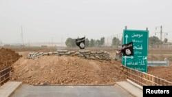 Islamic State flags flutter on the Mullah Abdullah bridge in southern Kirkuk, Iraq, Sept. 29, 2014.