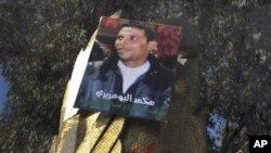 នៅក្នុងរូបឯកសារ ដែលបានថតនៅថ្ងៃទី ១៩ ខែមករា ឆ្នាំ២០១១ បង្ហាញអំពីក្រុមយុវជនប្រមូលផ្តុំគ្នានៅក្រោមរូបថតរបស់យុវជន Mohamed Bouazizi ក្នុងក្រុង Sidi Bouzid កណ្តាលប្រទេសទុយនេស៊ី។ ការស្លាប់របស់យុវជន Mohamed Bouazizi បានធ្វើឲ្យមានការបះបោរនៅប្រទេសអារ៉ាប់ផ្សេងៗទៀត។ (AP Photo/Salah Habibi)