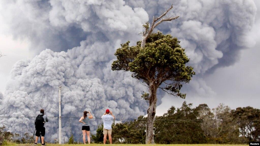 Residentes observan la expulsión de cenica del volcán Kilauea en la Isla Grande de Hawái el martes, 15 de mayo, de 2018.