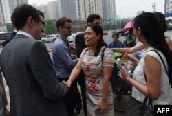 Fan Lili (C), the wife of detained activist Gou Hongguo, and other wives of detained layers meets with foreign diplomats near an office of the Supreme People's Procuratorate after attempting to hand in a formal complaint about being denied access to their husbands, in Beijing on July 4, 2016.