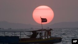 A Cambodian flag on a fishing boat flutters in wind as the sun sets over the Gulf of Thailand near Cambodia's port town of Sihanoukville.