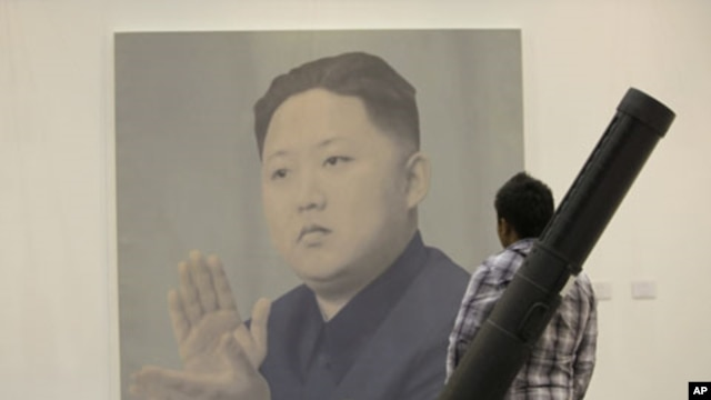 A man looks at a portrait of North Korean leader Kim Jong Un by Chinese artist Yan Lei at the China International Gallery Exposition 2012 in Beijing, April 13, 2012.
