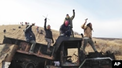 Protesters against the Dakota Access oil pipeline stand on a burned-out truck that they removed from a long-closed bridge on Sunday on a state highway near their camp in southern North Dakota, Nov. 21, 2016.