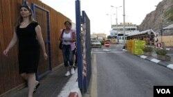 Dua warga melewati terminal Taba di kawasan Semenanjung Sinai Mesir, dekat kota perbatasan Eilat, Israel (18/8).