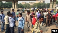 Scores of daily wage workers wait at a major street intersection in the business hub of Gurgaon near New Delhi hoping to find work. (A. Pasricha/VOA)