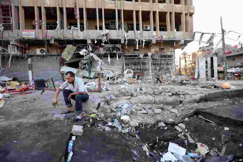 An Iraqi man inspects the site of a car bomb attack in central Baghdad's busy commercial Karradah neighborhood, Aug. 13, 2014.