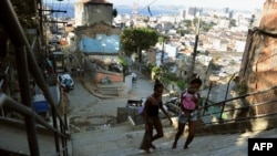 Locals walk in the Morro Da Providencia shantytown in Rio de Janeiro, Aug. 17, 2012. Hundreds of families were evicted from Rio favelas because of preparation work needed for the 2014 FIFA World Cup and the 2016 Olympic Games.