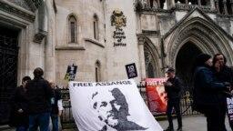 Sebuah spanduk yang bertuliskan dukungan terhadap pendiri WikiLeaks Julian Assange dipasang di luar gedung Pengadilan Tinggi London, pada 23 Oktober 2021. Spanduk tersebut dibentangkan menjelang pengadilan kasus ekstradisi Assange. (Foto: AP/Alberto Pezzali)