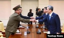 지난 2015년 8월 열린 남북 고위급 접촉에서 양측 대표들이 악수하고 있다.오른쪽부터 시계반대방향으로 한국의 김관진 국가안보 실장, 홍용표 통일부 장관, 북한의 김양건 노동당 비서, 황병서 군 총정치국장.