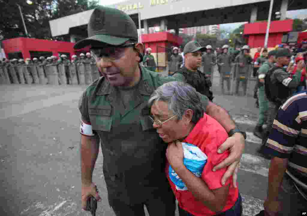 An army officer comforts a supporter of Venezuelan President Hugo Chavez outside the military hospital in Caracas, Venezuela, March 5, 2013.