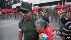 Seorang tentara mencoba menenangkan seorang pendukung Presiden Venezuela Hugo Chavez di luar rumah sakit tentara di Caracas, Venezuela (5/3). Jenazah Presiden Chavez akan disemayamkan di Akademi Militer sebelum dimakamkan hari Jumat mendatang.