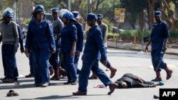 FILE: A protester lies unconsciously on the ground after being beaten by police near Unity Square in Harare on August 16, 2019.