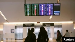 4月22日﹐旅客在加州三藩市國際機場查看飛機航班情況