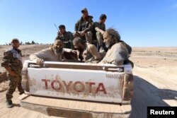 FILE - Islamic State fighters sit on a pickup truck while being held as prisoners by fighters of the Syrian Democratic Forces near Ash Shaddadi, Hasakah province, Syria, Feb. 18, 2016.