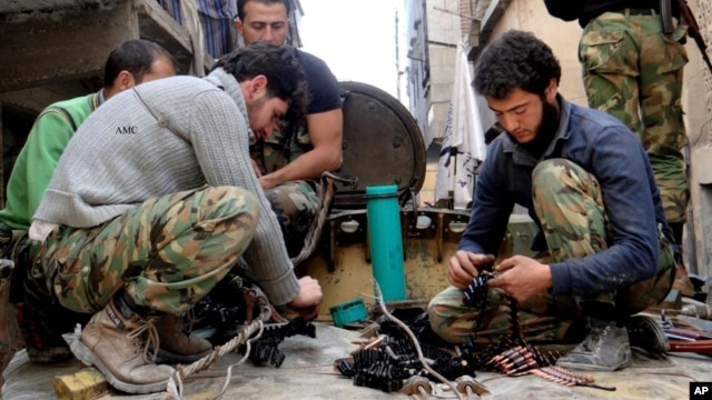 Citizen journalism image provided by Aleppo Media Center AMC which has been authenticated based on its contents and other AP reporting, shows members of the free Syrian Army preparing their weapons, April 25, 2013.